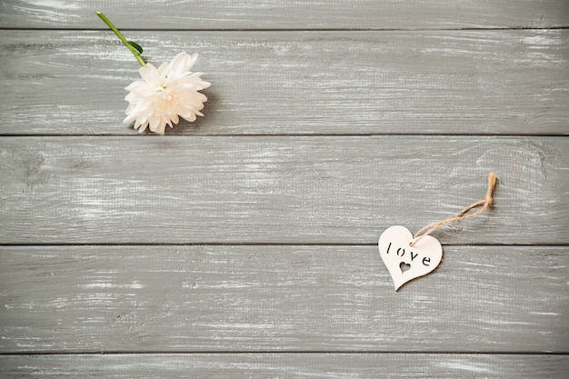 幸せなバレンタインデーの背景。灰色の素朴な花、バレンタインのコンセプトに装飾的な白い木の心。