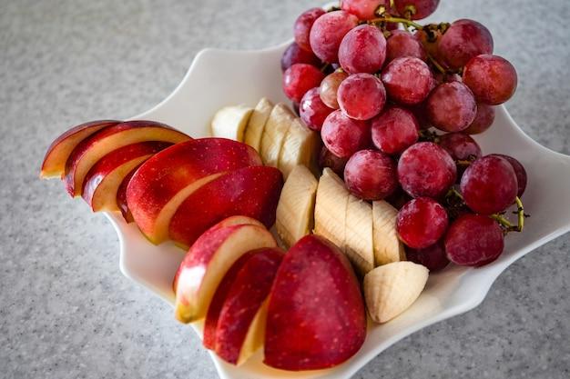 グレー、リンゴ、バナナ、ブドウのプレートにスライスされたフルーツ