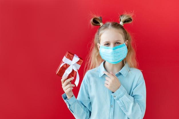 Девочка-подросток в маске держит подарочную коробку в руках, день рождения в хорошем настроении во время карантина, вызванного эпидемией коронавируса.