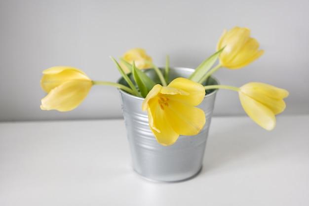 棚、インテリア、日当たりの良い部屋に抽象的な花瓶に美しい春の黄色いチューリップ