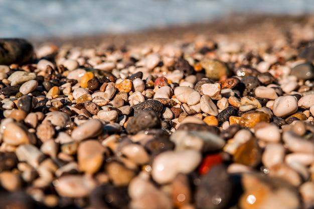 美しい澄んだ海。海岸の色の付いた海の小石を波が泳ぎました。