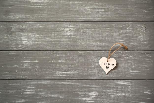 幸せなバレンタインデーの背景。素朴な灰色の装飾的な白い木の心。バレンタインのコンセプト。
