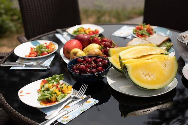 Летний пикник на природе, салат подается на тарелках.