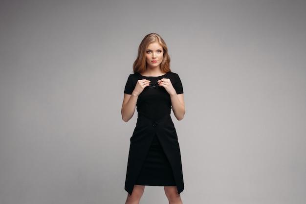 Женщина в длинном черном платье позирует