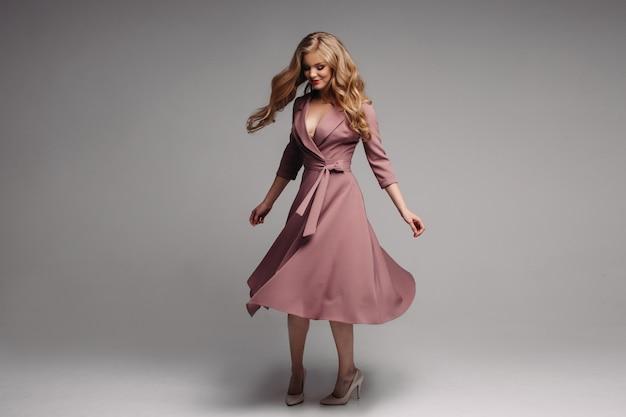 Симпатичная блондинка в длинном платье с чернилами и спиннинг