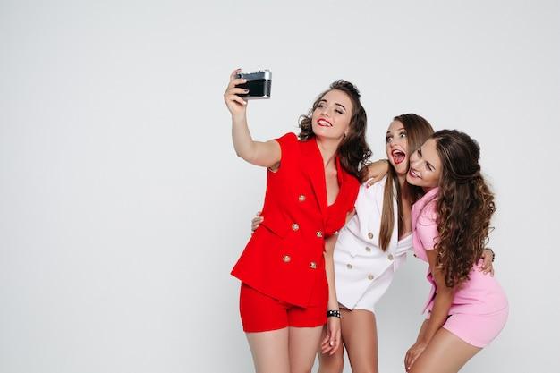 Модные девушки в ярких разноцветных костюмах снимают селфи через фильм
