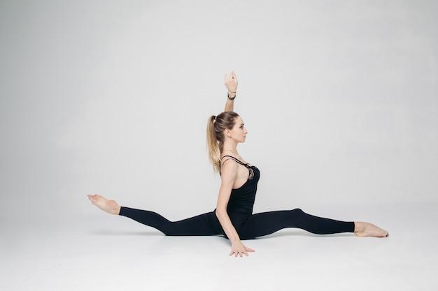 縦長の麻ひもに座っている運動の女性トレーニング。