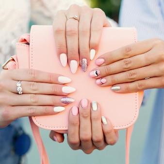 Две женщины с дизайнерским маникюром держат кожаную розовую сумку.