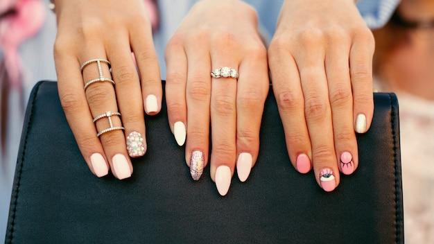 女性は彼女のスタイリッシュなマニキュアを見せ、黒いハンドバッグに指の指を保持しています。