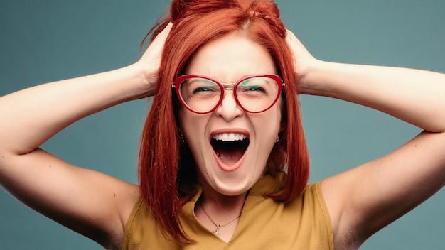 Истеричная женщина в очки, держа голову руками.