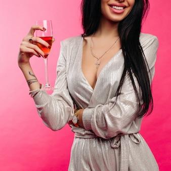 Улыбающаяся красавица в коктейльном комбинезоне с игристым вином.