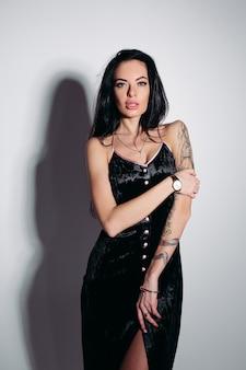 白い背景の上のタトゥーと黒のドレスでセクシーな女性。