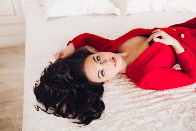 目を閉じてベッドに横になっている赤いドレスでセクシーな女の子。