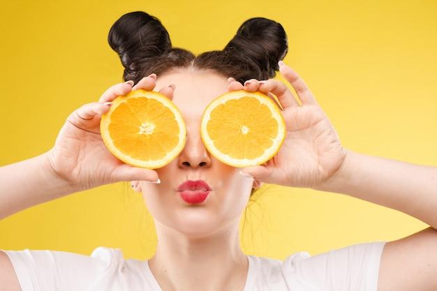 Смешная модная девушка с прической, держа апельсины на глазах.