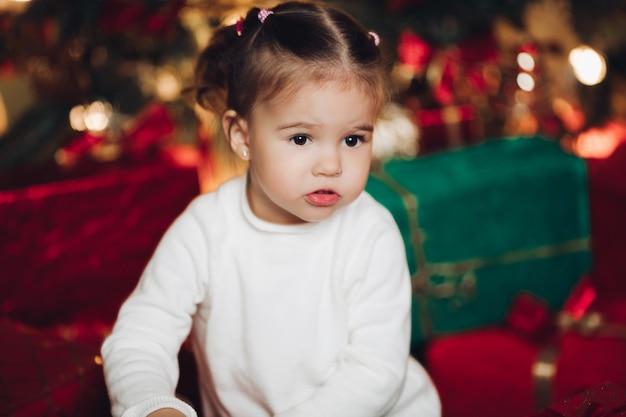 Очаровательны девочка в рождественские подарки. комната украшена на рождество.