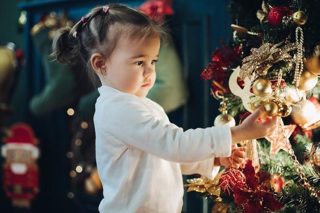 Милая маленькая девочка с елкой. вид сбоку очаровательной маленькой девочки