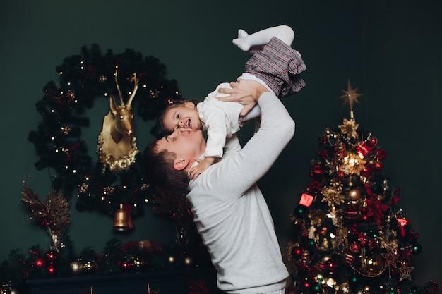 クリスマスに彼の娘と遊ぶ愛情のある父。