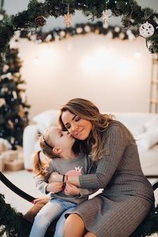 母と娘のクリスマススイング。クリスマスツリー。
