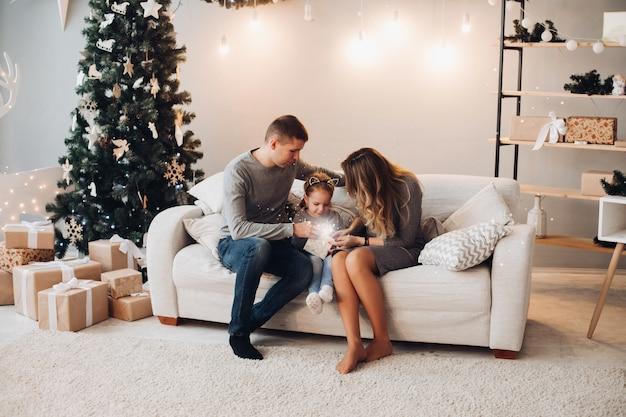 クリスマスプレゼントを開く子供連れの家族。クリスマスツリー。