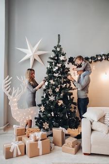 幸せな家族がクリスマスツリーを飾る。クリスマス