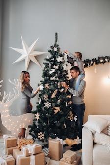 家族一緒にクリスマスツリーを飾る。クリスマスツリー。