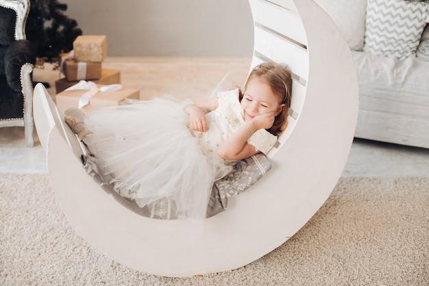 Маленькая девочка, лежа на уютной кровати в форме полумесяца.