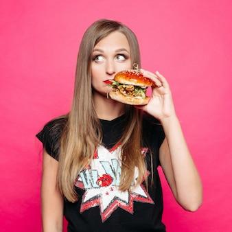 К сожалению девушка думает есть вкусный гамбургер или нет.