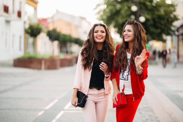 通りでスポーツシックなスーツとハンドバッグで女性を笑います。