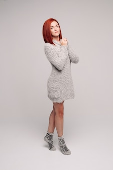 灰色のニットセーターと暖かい靴下を着ている赤い髪の少女。