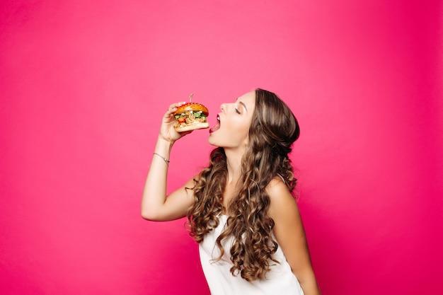 Голодная девушка с раскрытой пасти ест большой гамбургер.