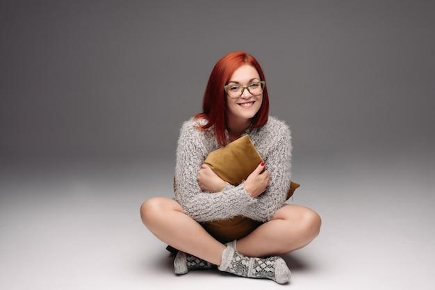 灰色のセーターと床に座って暖かい靴下で赤い髪の少女