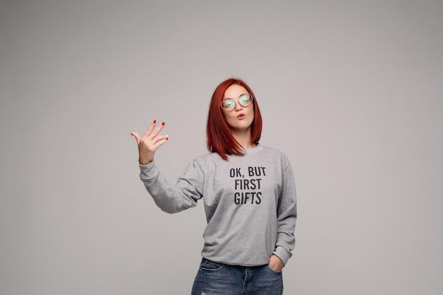 ジーンズとスウェットシャツの盗品と自信を持って赤い髪の少女