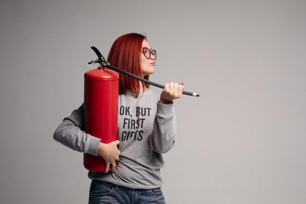 消火器を保持している赤い髪の女