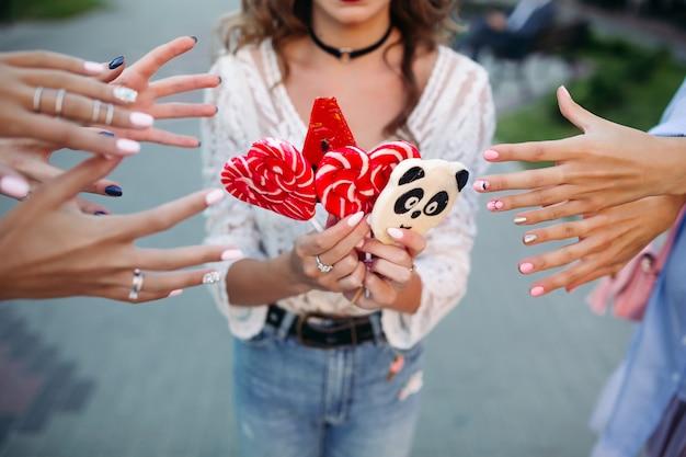 Девочка держит конфеты на палочке и руки трех девушек, протягивая руки, чтобы взять конфеты.