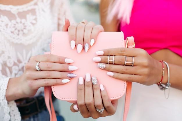 Девушки с дизайнерским маникюром держат кожаную розовую сумку.