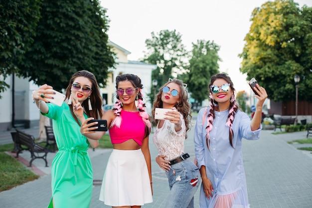 笑顔の女性がポーズし、スマートフォンでセルフポートレートをタックします。