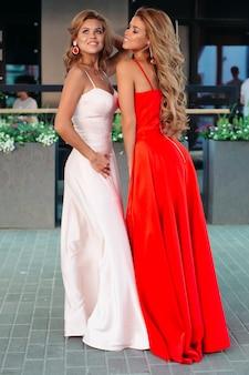 Великолепные и привлекательные женщины в длинных вечерних платьях позируют
