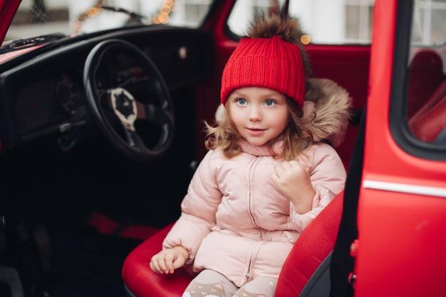車に座っている赤い帽子で笑顔のかわいい女の子