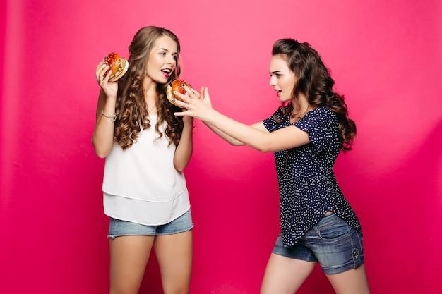 女の子は彼女の友人のハンバーガーを取りたいです。