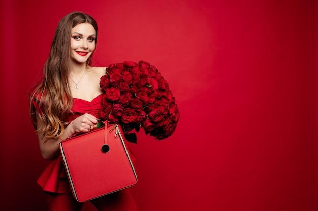 赤いバラと赤いバッグと赤でスタイリッシュな豪華なブルネット