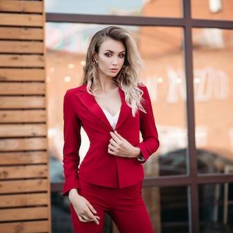 ゴールドボタンと濃い赤のスーツでエレガントな金髪女性