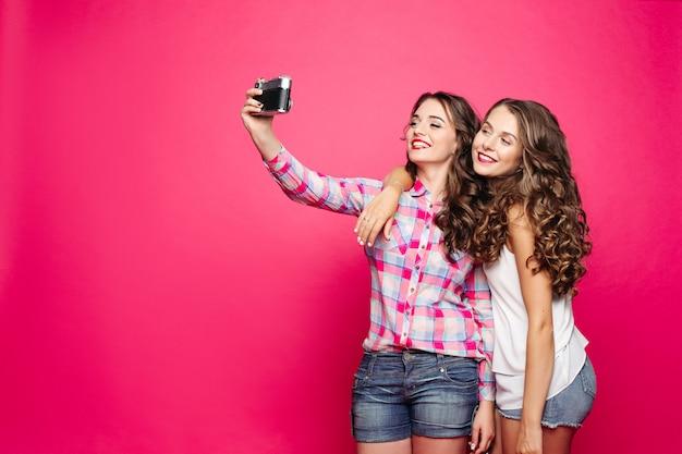 Очаровательные дружелюбные девушки, принимающие автопортрет через пленочную камеру.