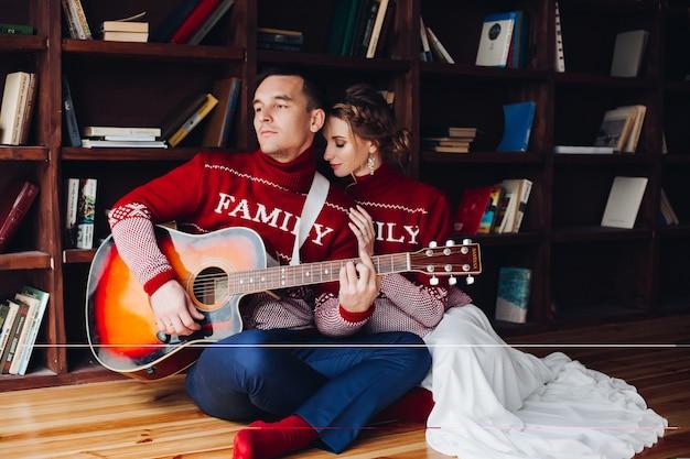 Пара играет на гитаре и обнимает