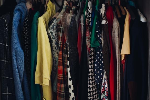 ファッショナブルな店のワードローブの異なる衣類のラック