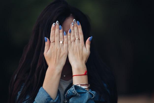 Девушка с шикарными темными длинными волосами прячет лицо руками