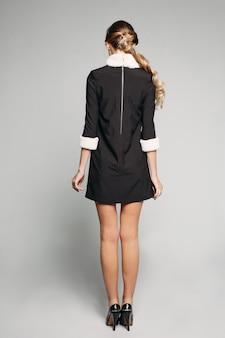 毛皮の襟と袖とハイヒールのミニ黒のドレスを着た金髪の女性。