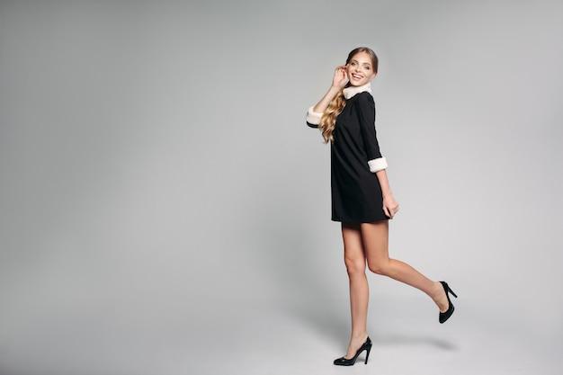 巻き毛のヘアスタイルがスタジオでジャンプアップと笑顔の陽性女性。