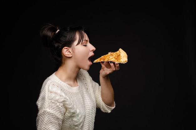 ピザを食べる尾を持つ若い白人女性。