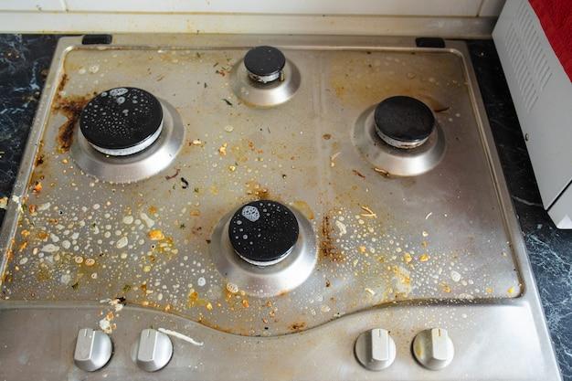 Процесс мойки газовой плиты. крупный план грязной газовой плиты, покрытой химической моющей жидкостью. концепция работы по дому или по дому.