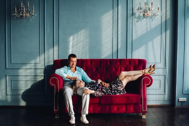 Элегантная пара стоит у классически украшенной стены с люстрами